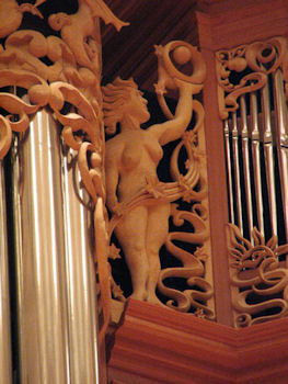 Life-sized wood carved sculpture of woman with orb, pipe shade carvings at Fritts organ at Pacific Lutheran University, master wood carver Jude Fritts