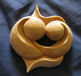Hand-held carving, two heads touching with intertwined hearts, personal wood art